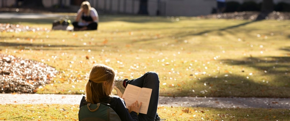 a students studies under fall leaves on historic North Campus at the University of Georgia in Athens